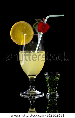 Glass of lemonade with bendie and orange slice and small glass of green drink on black mirror background with reflection - stock photo