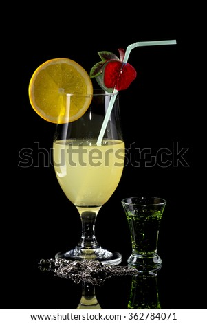 Glass of lemonade with bendie and orange slice and small glass of green drink on black mirror background with silver necklace with reflection  - stock photo
