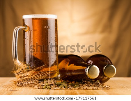 Glass of light beer  and bottles on table  - stock photo