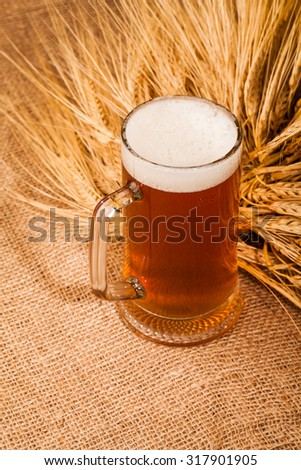 Glass of light beer and spikes of barley on table