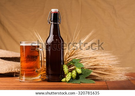 Glass of light beer and spikes of barley on table - stock photo