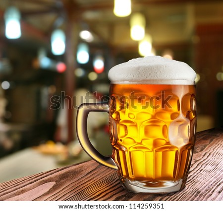 Glass of light beer on a dark pub. - stock photo