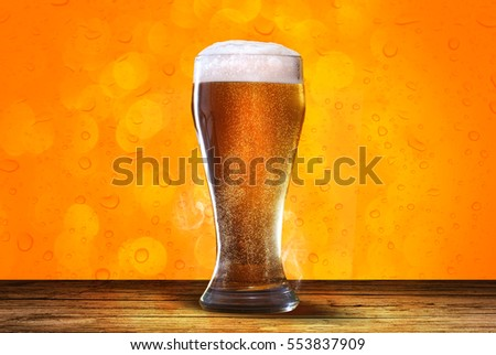 Glass of light beer on pub, bar, with wood table and orange background with bokeh, drop and smoke effect.