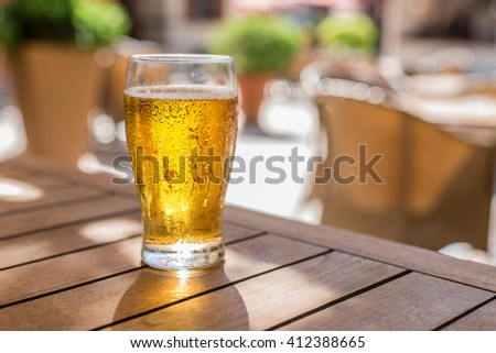 Glass of light beer on the wooden table. - stock photo