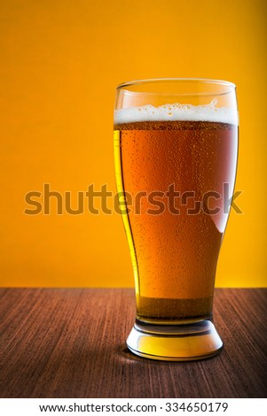 Glass of light beer on yellow background