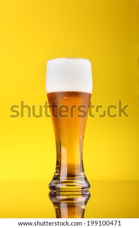 Glass of light beer over a bright yellow background