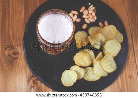 Glass of light beer with potato chips with salt peanut on the black tray on the wooden table in the pub. Friday night in the pub concept. Food and drink - stock photo