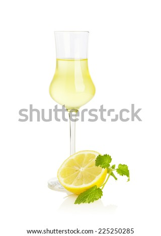 Glass of Limoncello liqueur with half lemon and mint leaf isolated on white background - stock photo
