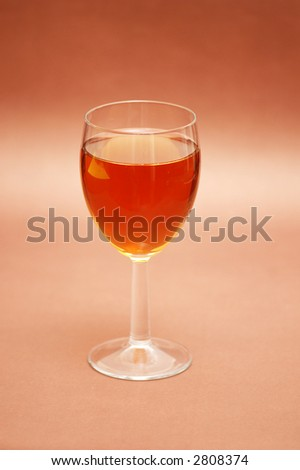 Glass of liqueur over the biege background - stock photo