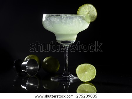 Glass of margarita cocktail on a black background. - stock photo