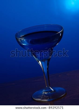 Glass of margarita on blue background