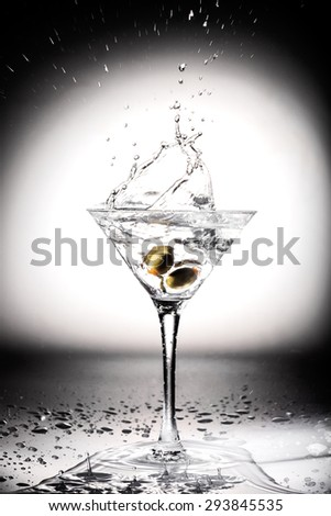 Glass of martini cocktail with olives and splashes - stock photo