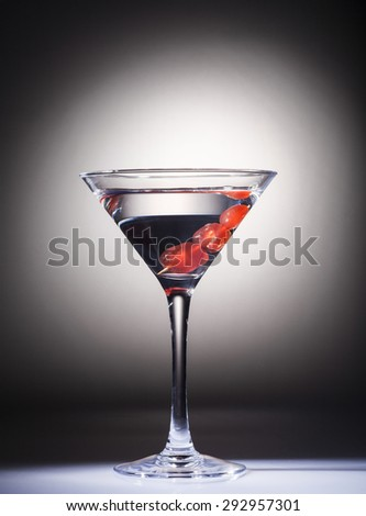 Glass of martini cocktail with red cherries on black and white background. - stock photo