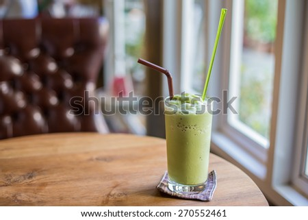 glass of matcha green tea frappe on wooden table. - stock photo