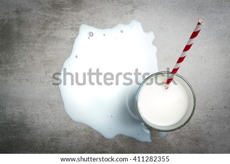 Glass of milk and a red and white drinking straw on a concrete table. It is a puddle of milk on the table. Crying over spilt milk. View from the above.