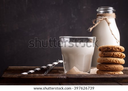 Glass of milk and chocolate chip cookies on wooden background - stock photo