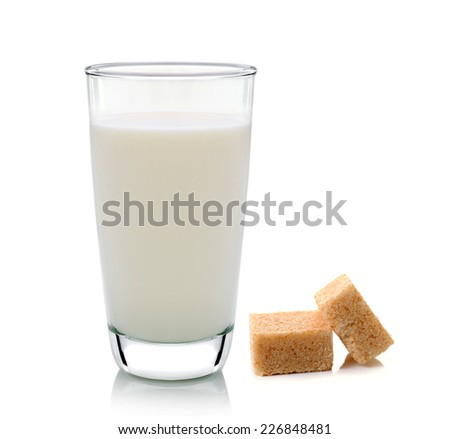 glass of milk and cubes of cane sugar isolated on white background