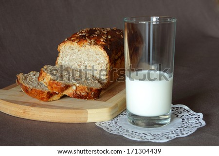 Glass of milk and freshly baked bread with a golden crust