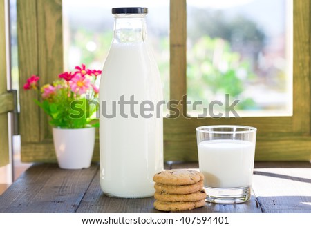 Glass of milk and homemade cookies next to a window