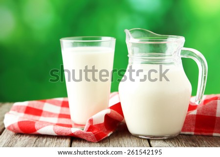 Glass of milk and jug of milk on grey wooden background - stock photo