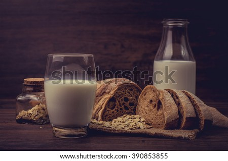 Glass of milk and pieces of brown bread on the table. - stock photo