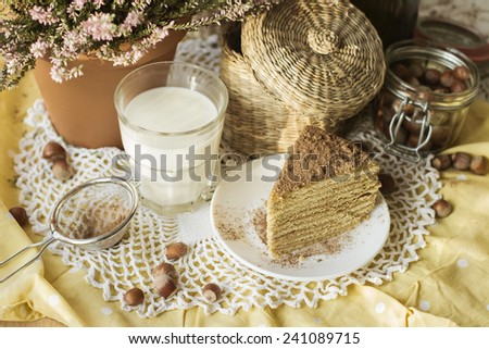 Glass of milk and tasty homemade delicious cake on plate on wooden table - stock photo