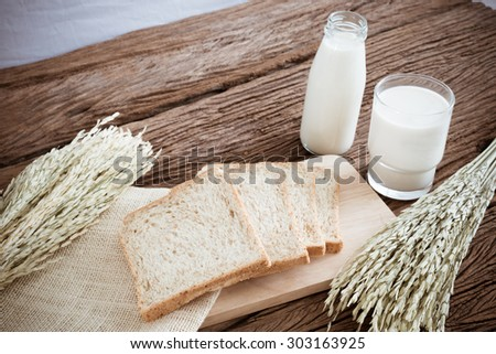 glass of milk and whole wheat bread on the wooden board. Retro style colour