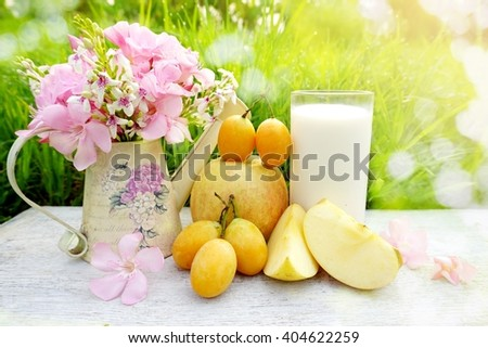 glass of milk, apple fruit and pink flower on white wood table with green grass nature bokeh light background in a garden  - stock photo