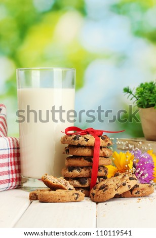 glass of milk, chocolate chips cookies with red ribbon and wildflowers on wooden table on green background - stock photo