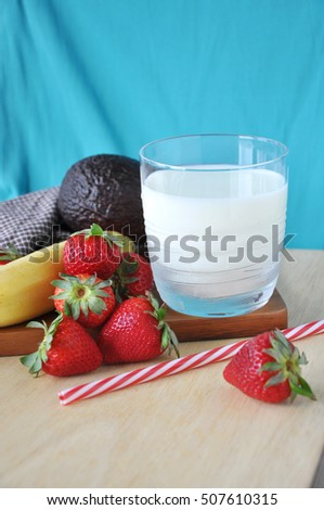Glass of milk fresh healthy fruits on wooden board and blue background