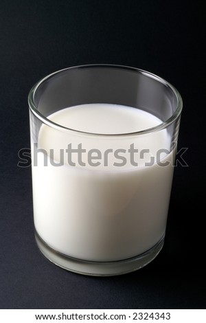 Glass of milk isolated in black background