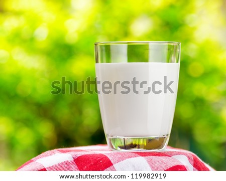 Glass of milk on nature background - stock photo