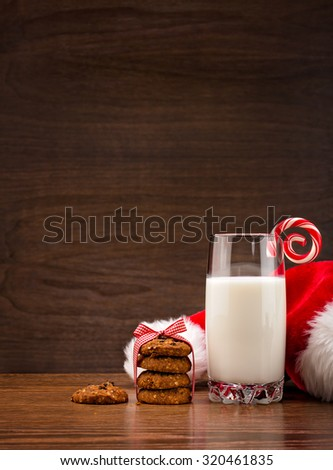 Glass of Milk with cookies and a candy cane for Santa over a wooden background