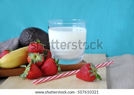 Glass of milk with fresh healthy fruits on wooden with blue background