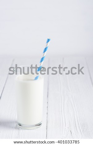 Glass of milk with paper striped straw on white wooden table - stock photo