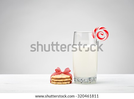 Glass of Milk with sugar cookies and a candy cane - stock photo