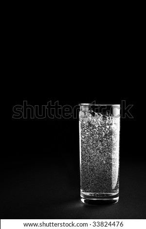 Glass of mineral water is isolated against a black background - stock photo