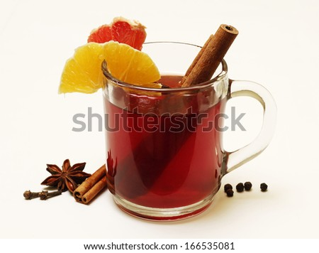 Glass of mulled wine and condiments isolated on white - stock photo
