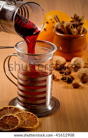 Glass of mulled wine being poured from jug with nuts and spices in background