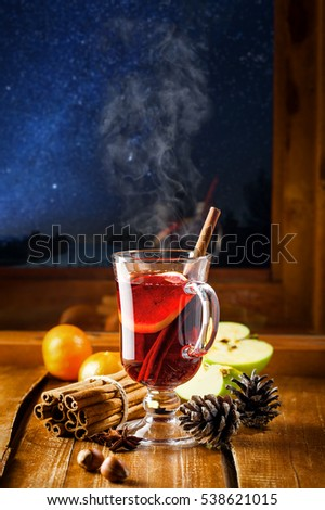 Glass of mulled wine on a table at window, winter night starry landscape on background. Traditional Christmas hot drink.