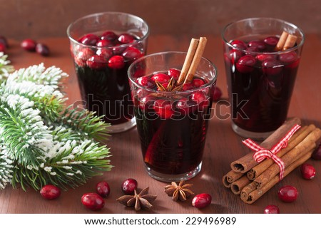 glass of mulled wine with cranberry and spices, winter drink - stock photo