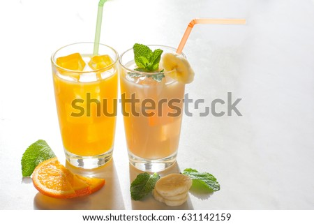 Glass of orange and banana juice with ice cube