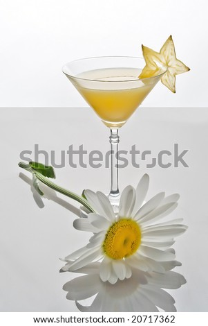 Glass of orange cocktail and camomile