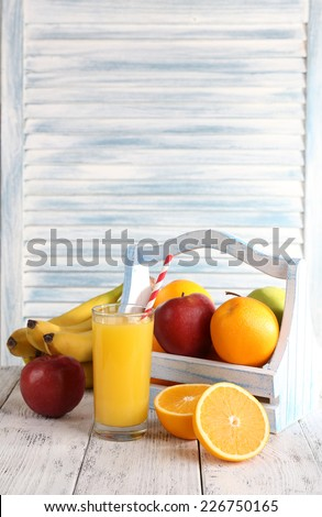 Glass of orange juice and fresh fruits in wooden box on wooden table on wooden wall background - stock photo