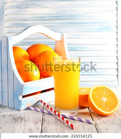 Glass of orange juice and fresh oranges in wooden box on wooden table on wooden wall background - stock photo