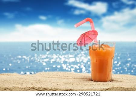 glass of orange juice and sand and sea  - stock photo
