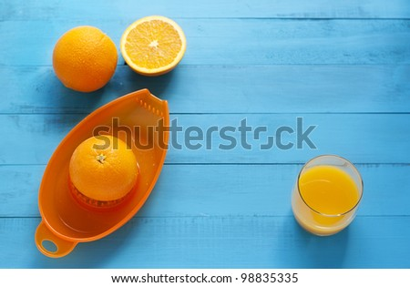 glass of orange juice and squeezed orange against blue table top - stock photo