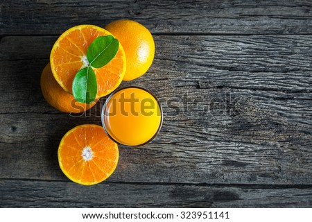 Glass of orange juice from above on wood table.orange juice on wood.orange juice in grass.orange juice above.orange juice color - stock photo