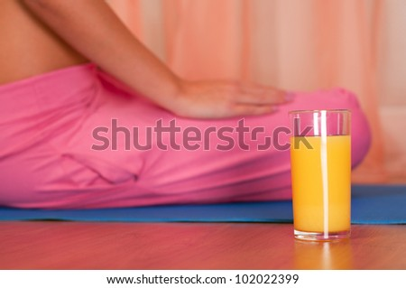 Glass of orange juice in front of sporty woman - stock photo