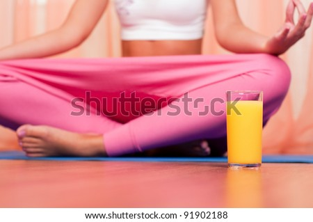 Glass of orange juice in front of sporty woman